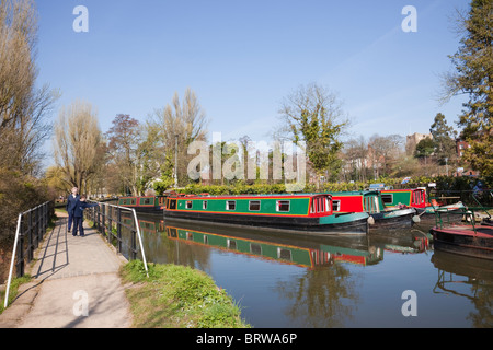 People walking on riverside path beside River Wey with canal boats moored on Godalming Navigation in Guildford Surrey - Stock Photo