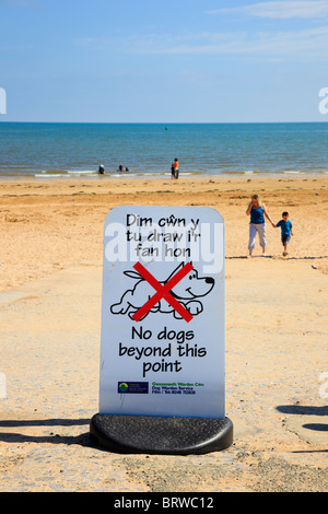 'No dogs beyond this point' sign on beach in Welsh and English in seaside resort in summer. Benllech, Anglesey, - Stock Photo