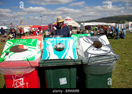 Man recycling at range of colourful recycling bins Greenbelt Festival 2010 Cheltenham UK - Stock Photo