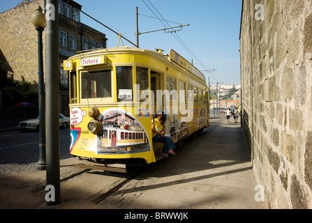 Ticket sales girl sits on the steps of a yellow tram which is used as the ticket sales office in Porto. - Stock Photo