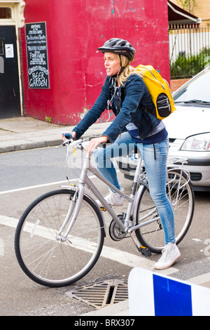 Camden Town , beautiful pretty young teenage blond girl on bike or bicycle chats to friend on hands free mobile - Stock Photo
