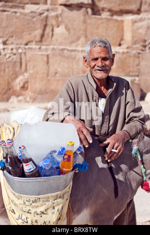 Elderly Egyptian man selling refreshments at the base of the Great Pyramid, Giza, Egypt. - Stock Photo