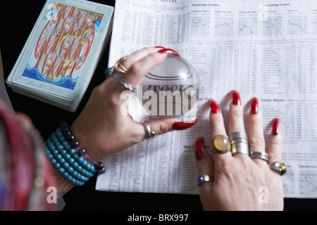 Fortune teller looking at newspaper financial pages through crystal ball, close-up of hands - Stock Photo