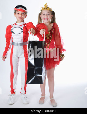 Studio portrait of boy and girl (10-11) wearing costumes and holding gift bag - Stock Photo