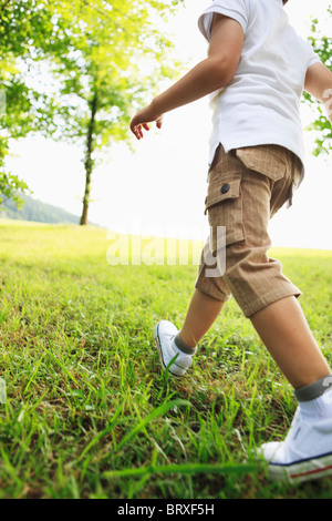 Low Section View of Boy Walking on Grass - Stock Photo
