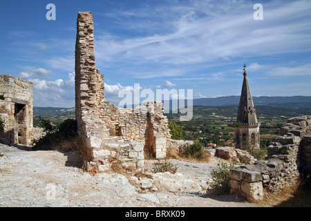 BELL TOWER OF THE VILLAGE CHURCH AND THE CHATEAU'S FORTIFICATIONS, SSAINT-SATURNIN-LES-APT, VAUCLUSE, FRANCE - Stock Photo
