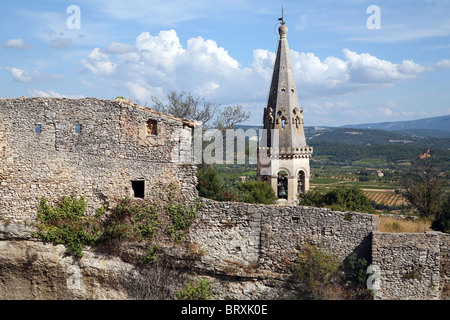 THE CHATEAU'S RAMPARTS AND THE CHURCH'S BELL TOWER, SAINT-SATURNIN-LES-APT, VAUCLUSE, FRANCE - Stock Photo