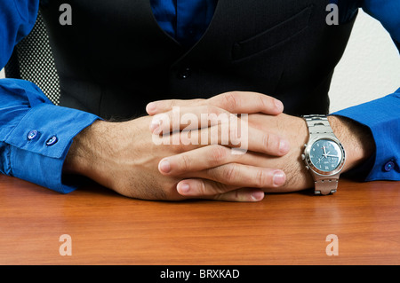 Close up of the body of a professional man sitting at a desk - Stock Photo