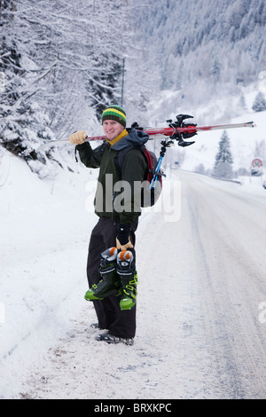 St Anton am Arlberg, Tyrol, Austria. Skier carrying ski boots with skis over his shoulder on snow covered Alpine - Stock Photo