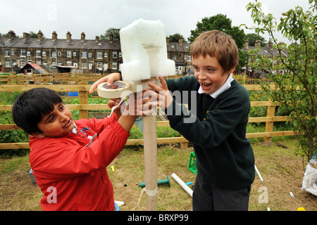 Children create models from waste packaging during a visit to local allotments, Bradford, West Yorkshire - Stock Photo