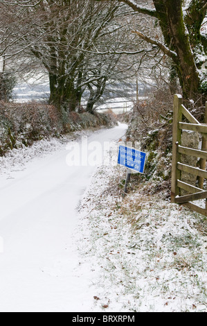 Narrow lane in snow with Unsuitable for vehicles over 6'0' wide sign, Dartmoor, Devon UK - Stock Photo