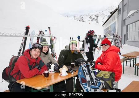 Skiers drinking in outdoor cafe on slopes at Galzig Bahn gondola station in Austrian Alps in winter. St Anton am - Stock Photo