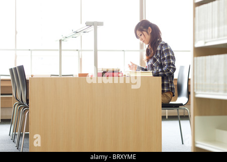 Young woman studying in a library Japan - Stock Photo