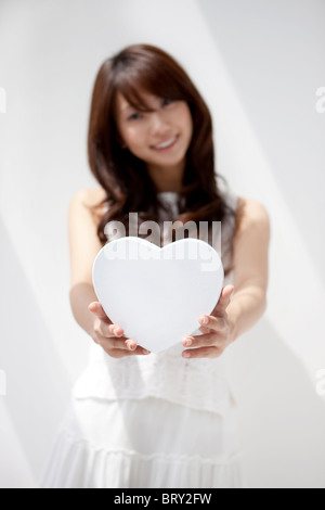 Portrait of young woman holding white heart shaped box, white background, differential focus - Stock Photo