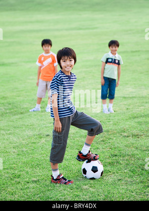 Portrait of boys playing soccer in field - Stock Photo