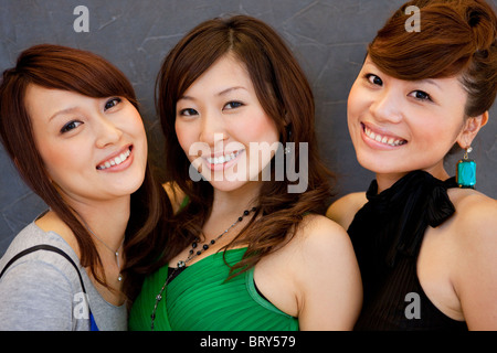 Portrait of three young women, smiling and looking at camera, black background - Stock Photo
