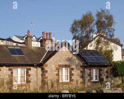 Water heating and photo voltaic electrical power generating solar panels on a house roof at Grange over Sands Cumbria - Stock Photo
