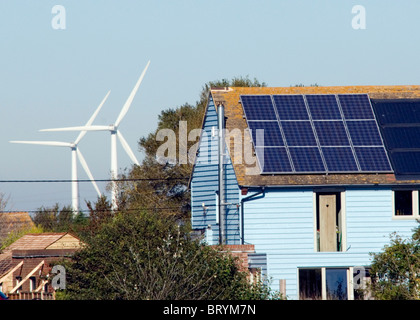 Wind turbines behind a house with solar panels The Recycled House Camber Rye east Sussex - Stock Photo