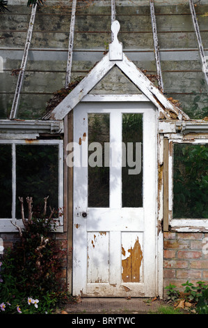 door of into an old decrepit victorian style greenhouse peeling paint disused disrepair - Stock Photo