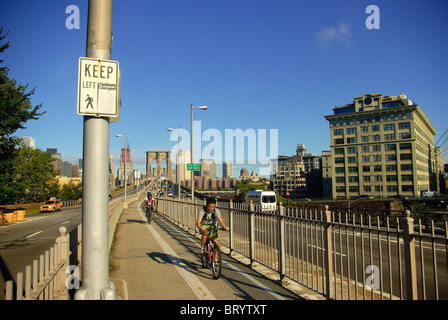 Cyclists riding in bicycle lane on Brooklyn Bridge in New York from High Street Brooklyn end - Stock Photo