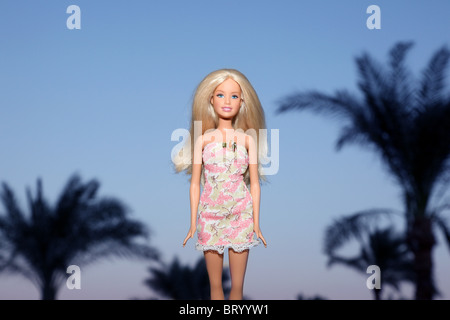 Barbie doll standing in front of Palm trees - Stock Photo
