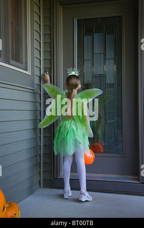 Girl (8-9) wearing fairy costume trick or treating, rear view - Stock Photo
