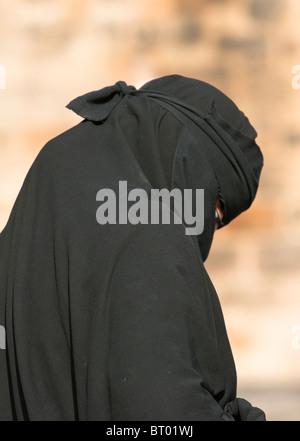Muslim woman wearing the Burka on the street in Britain. - Stock Photo