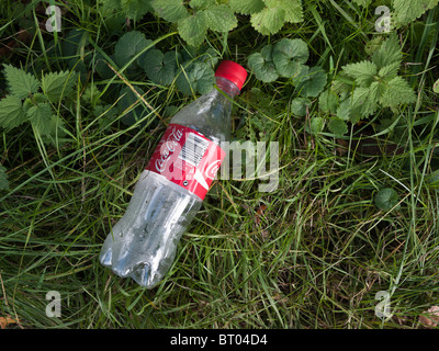 Plastic Coca Cola bottle discarded on grass roadside verge - Stock Photo