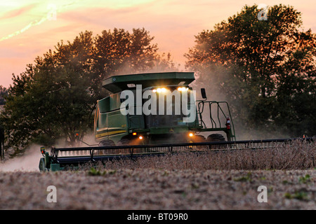 A John Deere 9670 STS combine picking soybeans at dusk. - Stock Photo