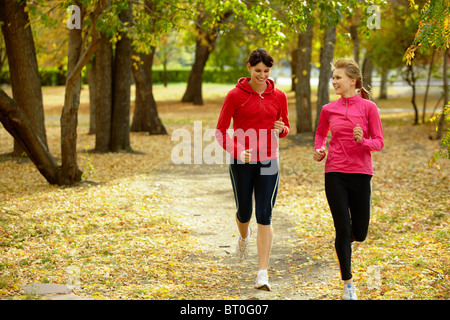 Two girls racing in autumn park - Stock Photo