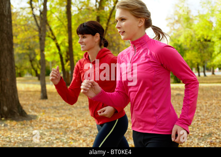 Two young women jogging in autumn park - Stock Photo