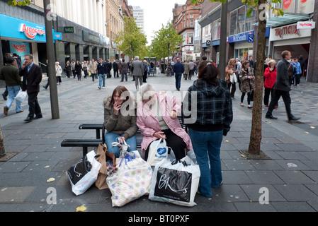 Female shoppers on Sauchiehall Street sitting smoking cigarettes with their bags of shopping Glasgow Scotland UK - Stock Photo