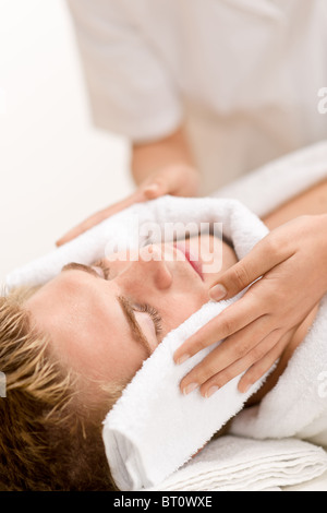 Male cosmetics - luxury spa treatment receiving facial massage - Stock Photo