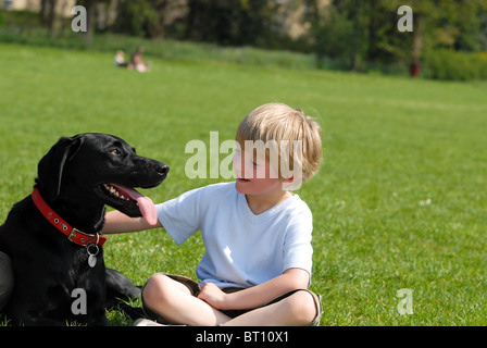 A happy little boy sitting on the grass smiling at his adored black Labrador dog which sitting by him panting in - Stock Photo