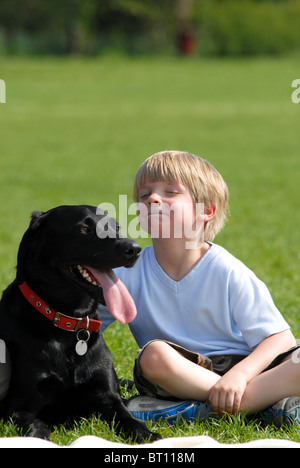 a happy little boy sitting on the grass next to his adored black Labrador dog which is panting in warm summer sun - Stock Photo