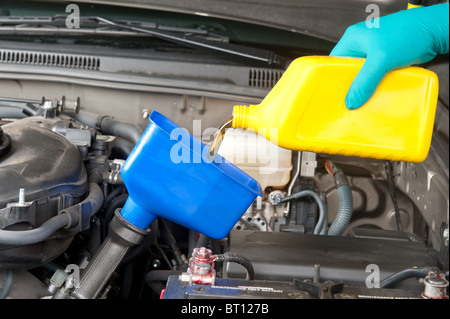 An automotive mechanic changes the oil in a modern car. - Stock Photo