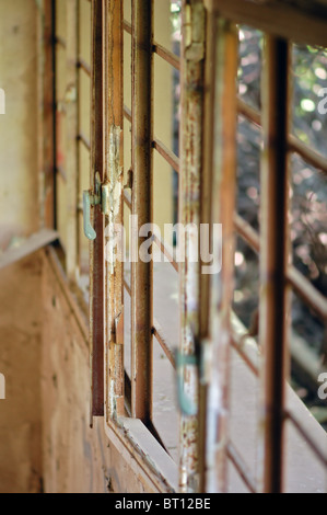 Rusty window frame in decaying house. Selective focus. - Stock Photo