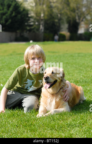 Blond-haired boy sitting on the grass in a park hugging his Golden Retriever pet dog on a hot sunny day - Stock Photo