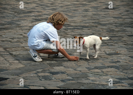 Man's best friend: boy gives dog a cup of water on a hot day in Italy - Stock Photo