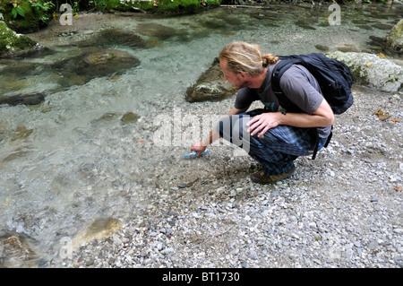 A male hiker takes a break to fill his water bottle at Kozjak brook, Kobarid, Slovenia September 2010 - Stock Photo