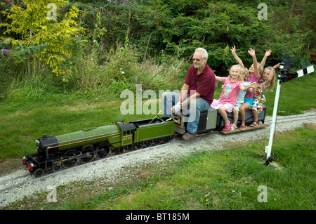 Three little girls waving as they ride a 5 inch gauge model  of 'Flying Scotsman' LNER train driven by a man with - Stock Photo