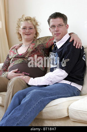 Pregnant couple sitting on couch, happy third trimester pregnancy - Stock Photo