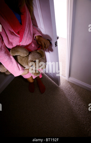 Child in a dark room alone holding a teddy bear - Stock Photo