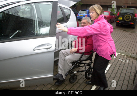 A wheelchair bound disabled man gets help from his carer wife UK - Stock Photo