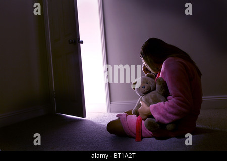 Little girl alone in a dark room holding a teddy bear, rear view. - Stock Photo