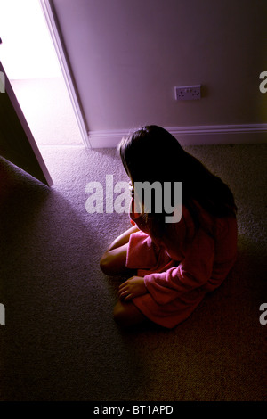 Young girl sitting on floor of a dark room light streaming into the room - Stock Photo