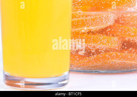 Orange cut in slices in fizzy water. Shallow depth of field, focus on the fizzy water. - Stock Photo