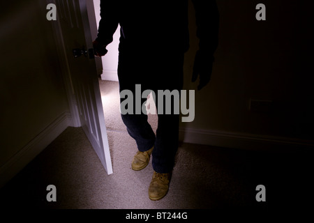Man wearing old boots entering a dark room turning the handle as he walks in - Stock Photo