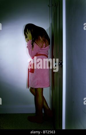 Young girl wearing a dressing gown in her bedroom, head in hands door closed. - Stock Photo