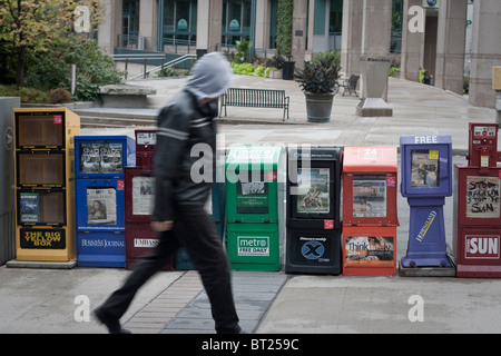 A man walks by newspapers boxes in Ottawa Sunday September 26, 2010. - Stock Photo